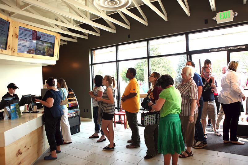 by: PAMPLIN MEDIA GROUP PHOTO: JAIME VALDEZ - People line-up to purchase an early lunch during the grand opening of Burgerville in Tigard located along Pacific Highway.