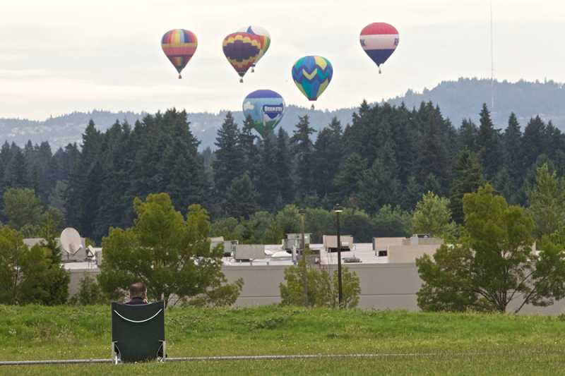 by: JAIME VALDEZ - Brian Johnson of Tualatin watches from Tualatin Elementary School as hot-air balloons rise from the trees. Johnson has been watching the balloons from the school since 2002.