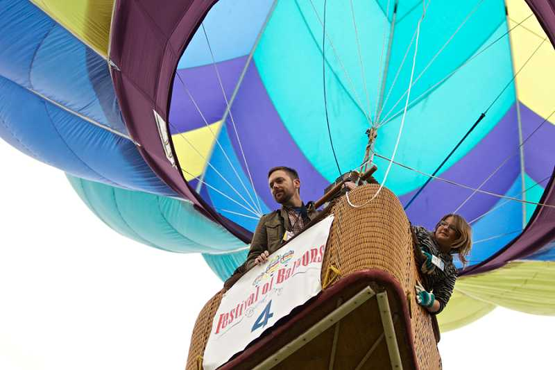 by: JAIME VALDEZ - The Times' Photgrapher Jon House and 11-year-old Grace Wyant guide Koh Murai's hot air balloon, 'Firenza' to a landing in Tualatin.