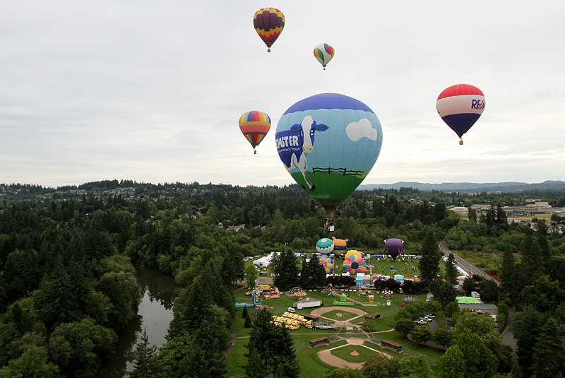 by: JONATHAN HOUSE - Michael Blum's balloon 'Beemster' rises from Cook Park, Friday, along with several other hot-air balloons. The Tigard Festival of Balloons features 24 giagantic balloons from across the country.