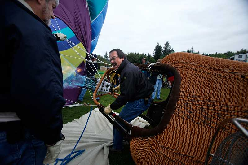 by: JONATHAN HOUSE - Koh Murai, of Yamhill, gives the command as his balloon 'Firenza' begins to inflate. Balloons are laid out on their sides and inflated with air, which raises them to a standing position.