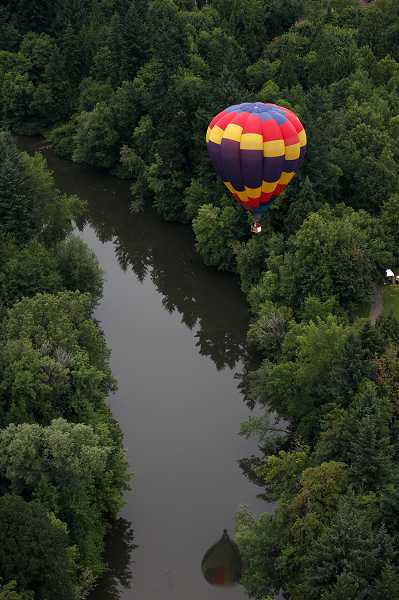 by: JONATHAN HOUSE - 'Padre Del Sol' piloted by Cheryl Issacs, of Tigard, floats over the Tualatin River. Balloon pilots often perform 'splash and dash' stunts where the balloon skims over the top of the water before rising again.