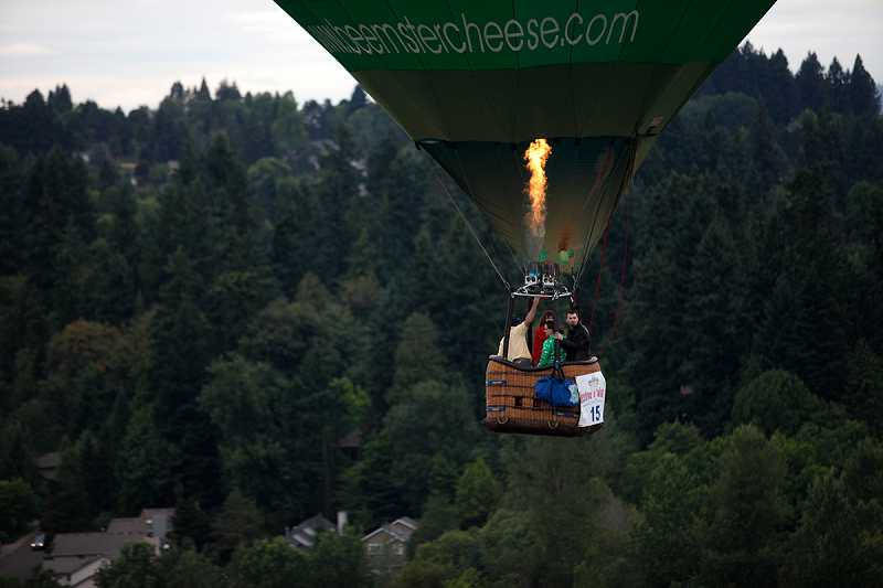by: JONATHAN HOUSE - Michael Blum fires more hot air into his balloon 'Beemster' as three passengers look out over Tualatin.