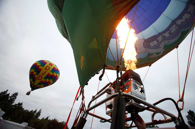 by: JONATHAN HOUSE - A burner breaths fire into the open envelope of a hot-air balloon during Friday's early morning balloon launch.