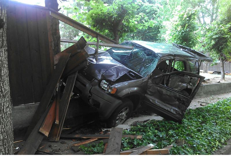 by: COURTESY OF BEAVERTON POLICE DEPARTMENT - The driver of a gray Ford Escape was seriously injured Sunday morning when the vehicle crashed into a fence and a wall on Southwest Brockman Street near Davies Road.