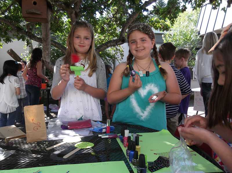 by:  KATE HOOTS - Fourth-grader Peyton Henry, left, sold pencil people and pins at her booth, while Lilly Curdy painted customers fingernails.