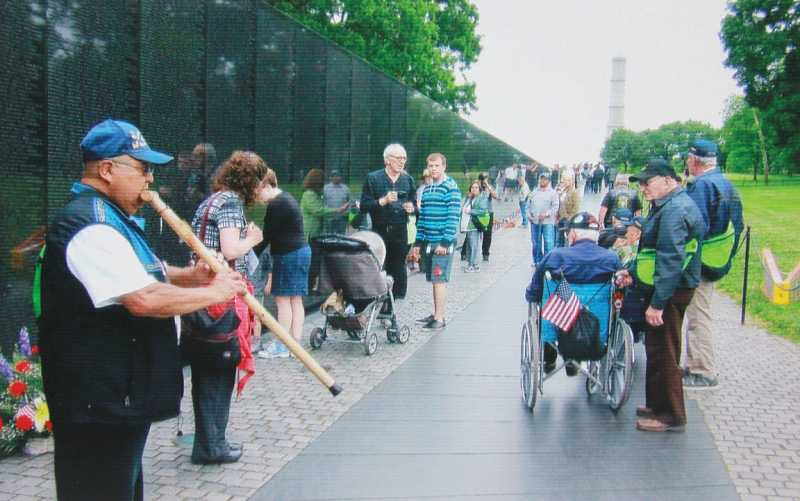Larson Kalama Sr. plays an honor song on his flute at the Vietnam War Memorial wall.