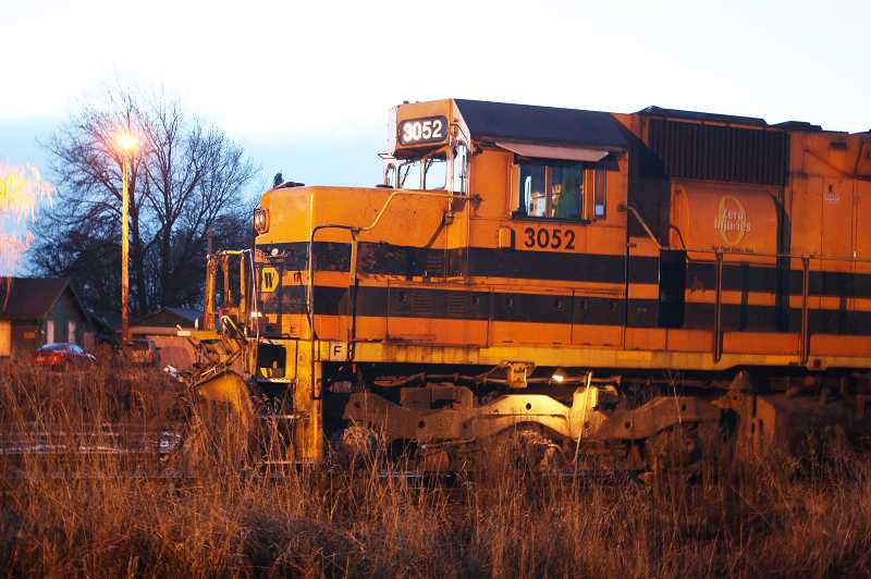 by: NEWS-TIMES PHOTO: DOUG BURKHARDT - Portland & Western locomotives roll through Banks at dusk after coming into the yard to reverse directions before taking a freight train toward North Plains. A new connecting track, about two-thirds of a mile long, will soon eliminate the need for trains to make the reversing move at Banks.