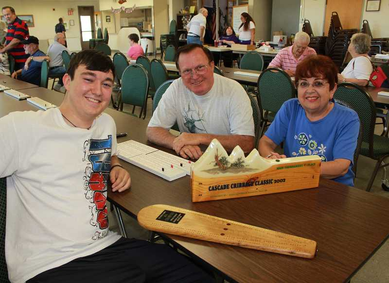 Ian, left, Marty and Irma Symons show off past cribbage trophies at Friday's match at the Jefferson County Senior Center.