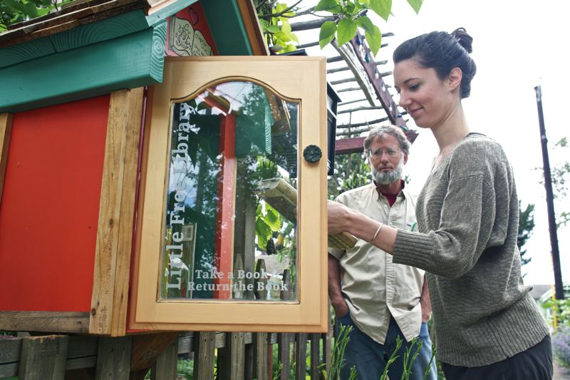 by: TRIBUNE PHOTO: JAIME VALDEZ - Volunteer Danielle Olson and Lents advocate Rusty Bonham checks out the books at one of the mini-libraries in the neighborhood.
