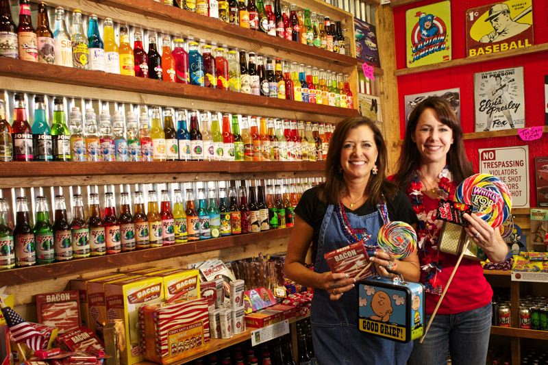 by: TIMES PHOTO: JAIME VALDEZ - Lori Joel, left, and Kristin Allen are making the most of their new business venture, Rocket Fizz Candy Shop and Soda Pop, at Progress Ridge TownSquare. Some of the oddly flavored and named sodas are on display, such as Judge Wapner Root Beer, above left.