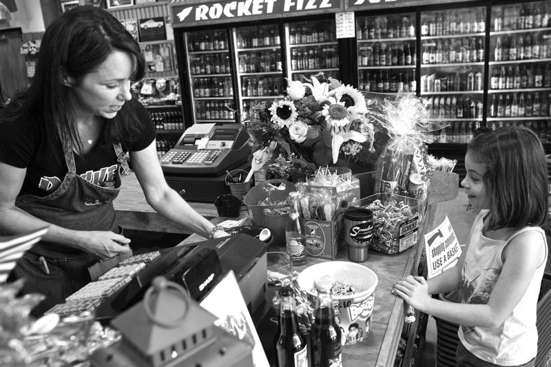 by: TIMES PHOTO: JAIME VALDEZ - Kristin Allen, co-owner of  Rocket Fizz Candy Shop and Soda Pop store at Progress Ridge TownSquare, helps Zoe Tyler, 7, purchase candy at the store on Monday morning.