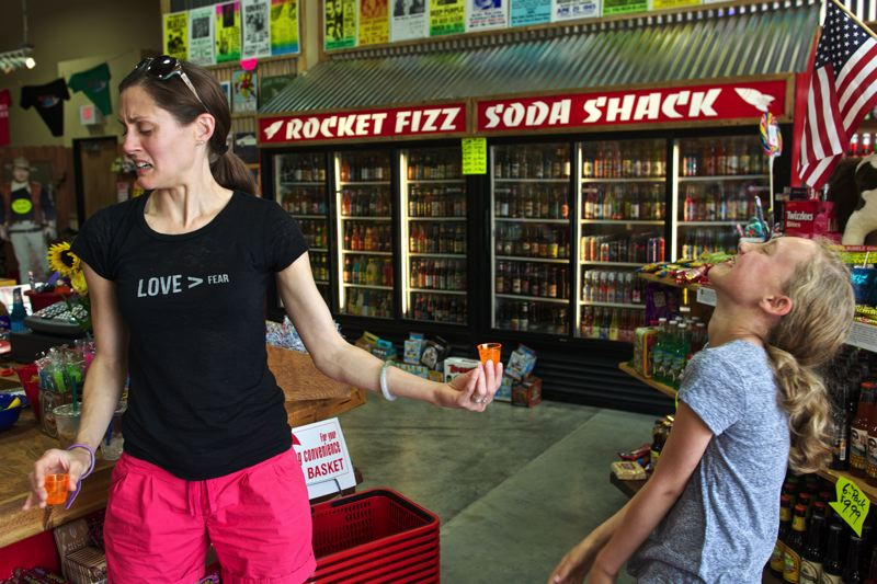 by: TIMES PHOTO: JAIME VALDEZ - Kara Ebbutt of Sexton Mountain reacts after sampling sweet corn soda pop as her daughter, Sophia, 11, laughs on Monday at the new Rocket Fizz Candy Shop and Soda Pop at Progress Ridge TownSquare.