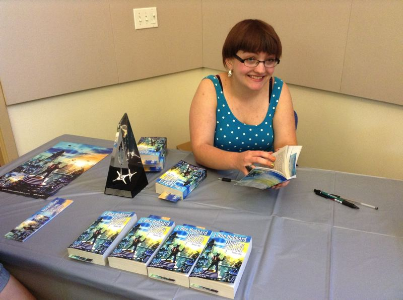 by: ESTACADA PUBLIC LIBRARY - Marilyn Guttridge signs a copy of L. Ron Hubbard Presents Writers of the Future, Volume 29, on Saturday, June 29, at the Estacada Public Library. Her short story, The Ghost Wife of Arlington, is featured in the anthology.