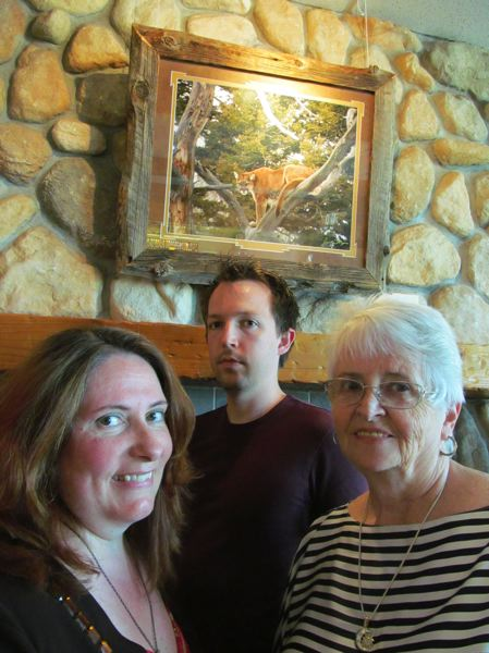 by: PHOTO BY: DICK TRTEK - Darla Lynn, left, president of the Three Rivers Artist Guild, and Jeff Willard, an artist and employee of the OC Haggen, join Rhondi Myra standing under the photo of a cougar taken by her husband, Jerry Myra.