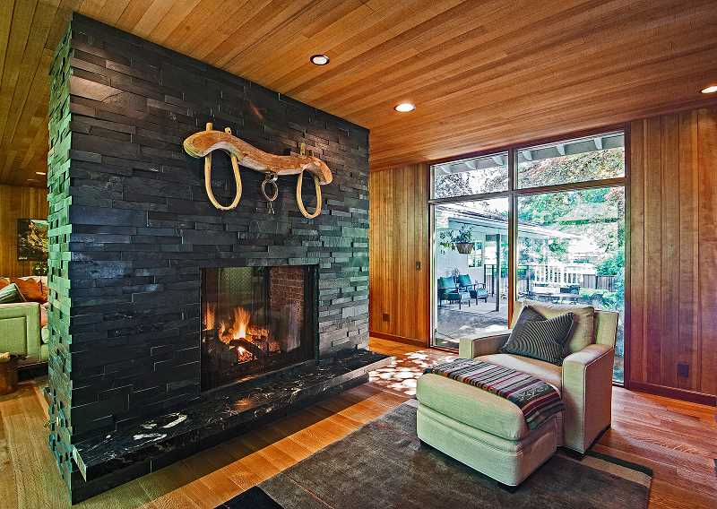 by: PAMPLIN MEDIA GROUP: JOSH KULLA - A double-sided fireplace is the new focal point in this Wilsonville ranch-style home. It acts as a natural, yet open, divider between the living room and the library.
