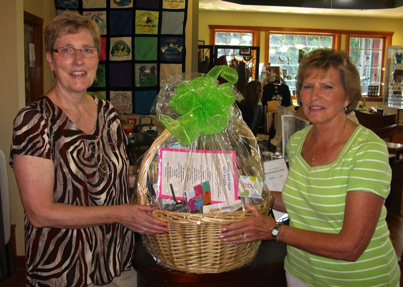 by: CONTRIBUTED PHOTO:  - Ann Marie Amstad of the Sandy Historical Society Museum, left, presents Rosemarie Stolz of Boring with the gift basket she won in a fund-raising drawing at the 2013 quilt show. The basket contained more than $500 worth of gifts donated by local businesses.