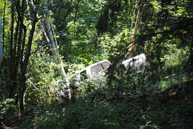 by: CONTRIBUTED PHOTO:  - Firefighters were perched in a very precarious place as they attempted to rescue a girl inside the pickup that had plunged off Bluff Road and stopped about 40 feet down a 500-foot cliff above the Sandy River.