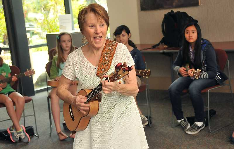 by: TIDINGS PHOTO: VERN UYETAKE - Cinda Johnson leads a group sing-a-long during her ukulele class June 27 at the West Linn Public Library.