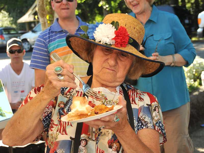by: TIDINGS PHOTO: VERN UYETAKE - Local activist Alice Richmond tastes a pie.