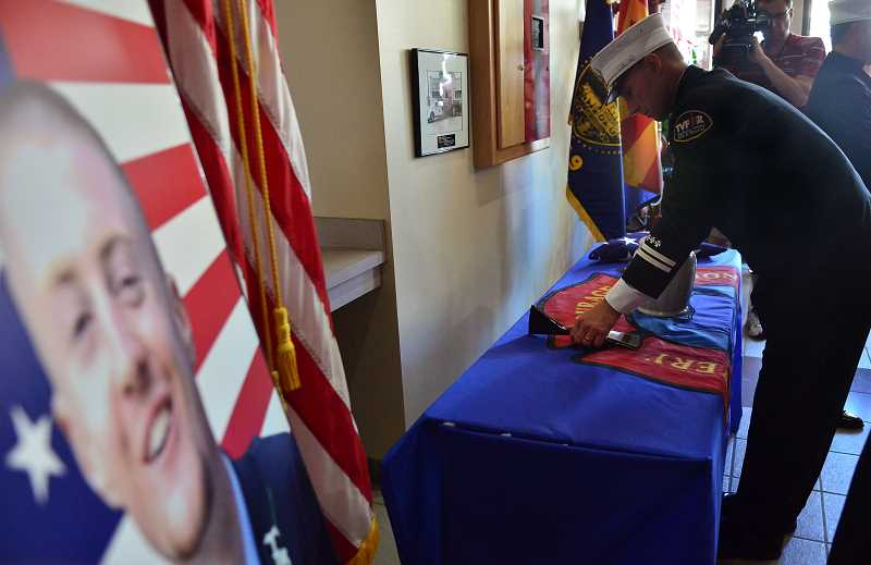 by: VERN UYETAKE -  A table was set up inside the doors of the Lake Oswego Main Fire Station with the urn along with a helmet and a flag, which will be held under vigil until the service.