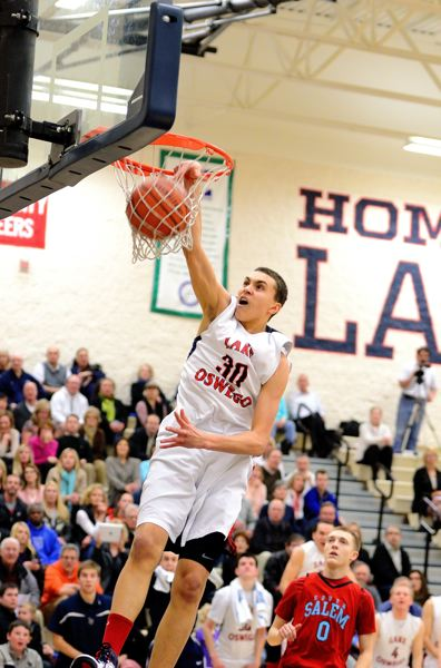 Natan Jurkovitz throws down a dunk during a Lake Oswego High School basketball game last season. His future is bright, but his present is questionable due to an OSAA ruling.