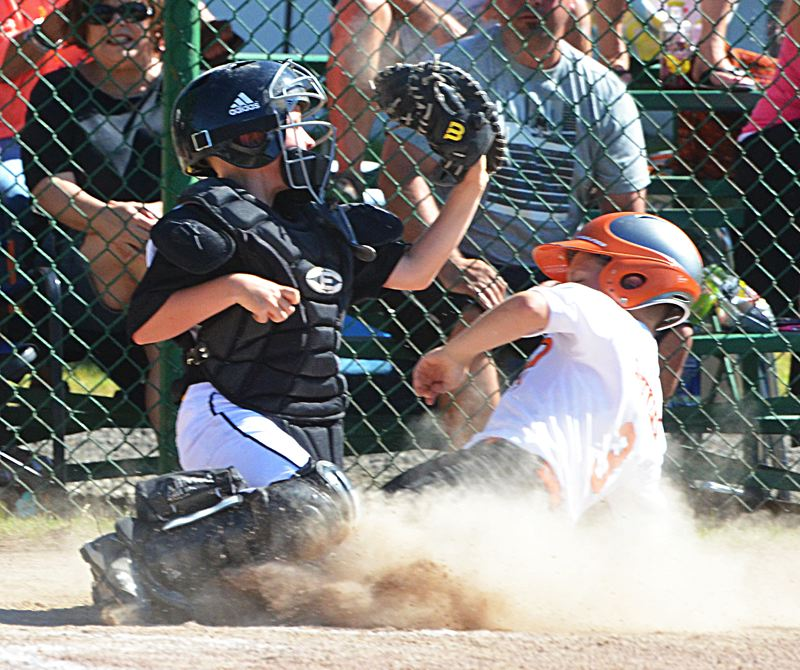 by: JOHN BREWINGTON - Scappoose's Tyler Souvenir slides home safely as Cameron Sexton tries to make a tag during the opening game of the Little League District 1 tournament.