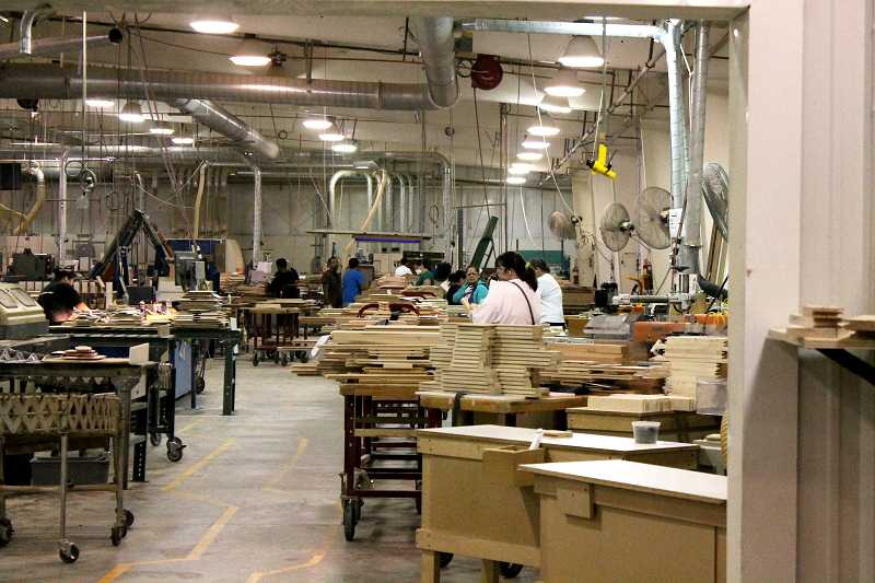 by: CORY MIMMS - Brentwood Corp. employees working to produce cabinet doors.