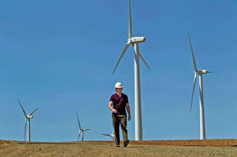 by: PAMPLIN MEDIA GROUP: JAIME VALDEZ - Art Sasse, communications director for Iberdrola Renewables in Portland, walks by wind turbines at the companys Klondike wind farm near Wasco, Ore.