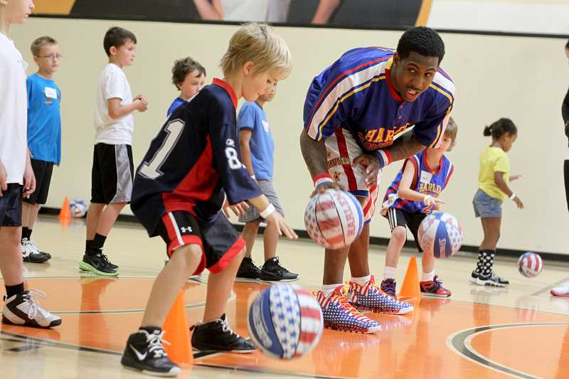 by: TIMES PHOTO: JONATHAN HOUSE - Harlem Globetrotter William 'Bull' Bullard shows young athletes how to properly dribble during a summer skills course at the Murray-Scholls 24-Hour Fitness on Tuesday.