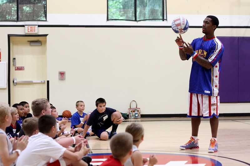 by: TIMES PHOTO: JONATHAN HOUSE - Harlem Globetrotter William 'Bull' Bullard shows off his basketball spinning technique during a summer skills course.