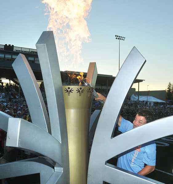 by: GARY ALLEN -  Tim Siler, of Newberg, a member of the Yamhill County team, lights the Olympic flame during the opening ceremony Saturday evening.