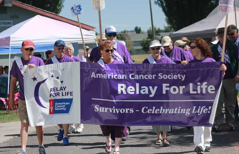 by: BILLY GATES - Carrying the Relay banner during the opening survivors' lap are Carlos Kemper, left, Rob Osborn, Cherie Gaddis, Helen Houts and Minda Morton.
