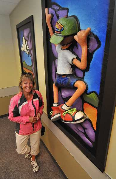 by: VERN UYETAKE - Artist Lori Russell stands next to one of the three-dimensional paintings she contributed to the Department of Human Services office in Oregon City.