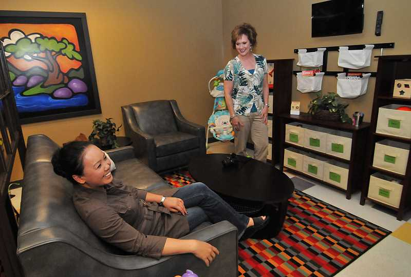 by: VERN UYETAKE - Sokpak Bhell, left, and Cindy Conlin admire one of the new child visitation rooms at the DHS building in Oregon City.