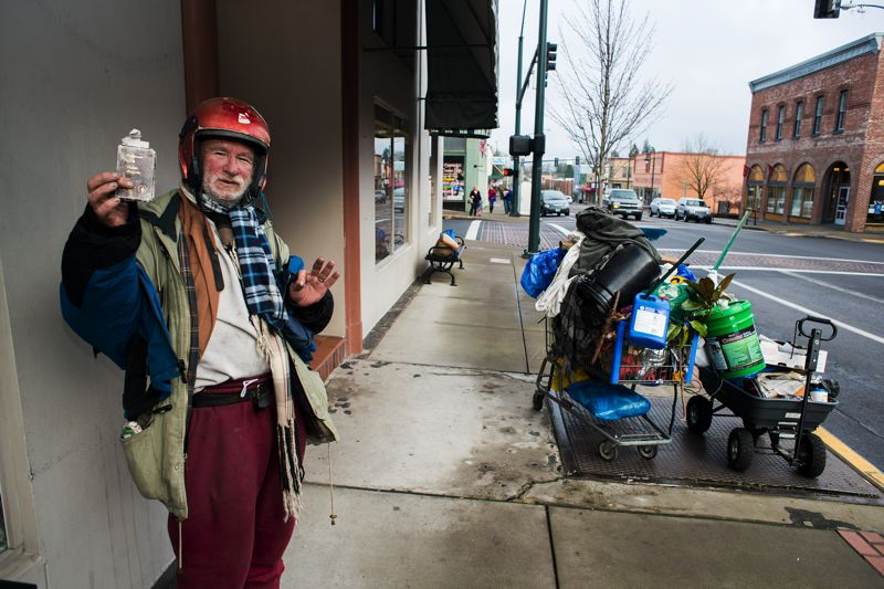 by: NEWS-TIMES PHOTO: CHASE ALLGOOD - John Wedell holds up his planetary booklet on Pacific Avenue near Grendels, one of his favorite restaurants (he loves the cheese toasties).
