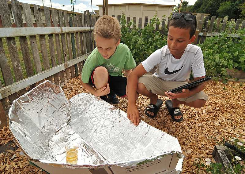 by: REVIEW PHOTO: VERN UYETAKE - Chris Burdick, left, and Clay Lucas, both seventh-graders, use a solar reflector to make biodiesel out of cooking oil.