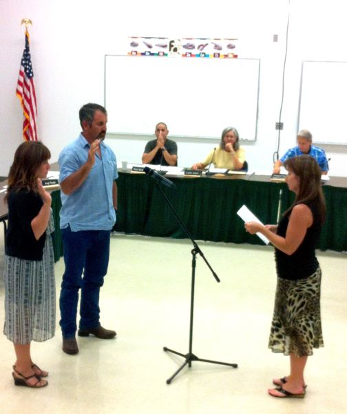 by: PHOTO BY NICOLE ADAMSON - Sabrina LaLonde, executive secretary and human resources administrative assistant for the Estacada school district, swears in new school board members Angela Riedel and Jeromy Adamson.