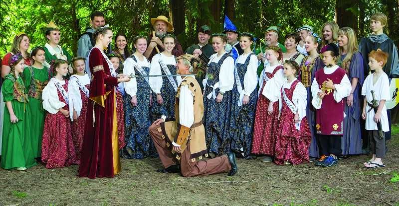 by: COURTESY PHOTO: LISA DILLION - This year's Maid Marian, Katy Roach, knights a loyal subject as her court, Robin Hood, his Merry Men and others look on.