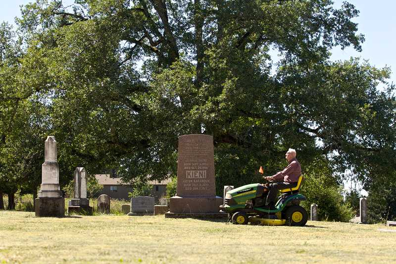 by: TIMES PHOTO: JAIME VALDEZ - From time to time, you will see Carl Bartruff and his wife Patricia riding lawn mowers and mowing the five acres of grass at Union Schoolhouse Cemetery located along Northwest 143rd Avenue in Cedar Mill. The original caretaker of the cemetery, George Foege, asked Carl to take over mowing the lawn 35 years ago.
