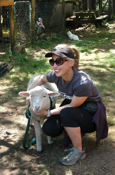 by: ISABEL GAUTSCHI - Volunteer Melissa Li poses with a rambunctious lamb.