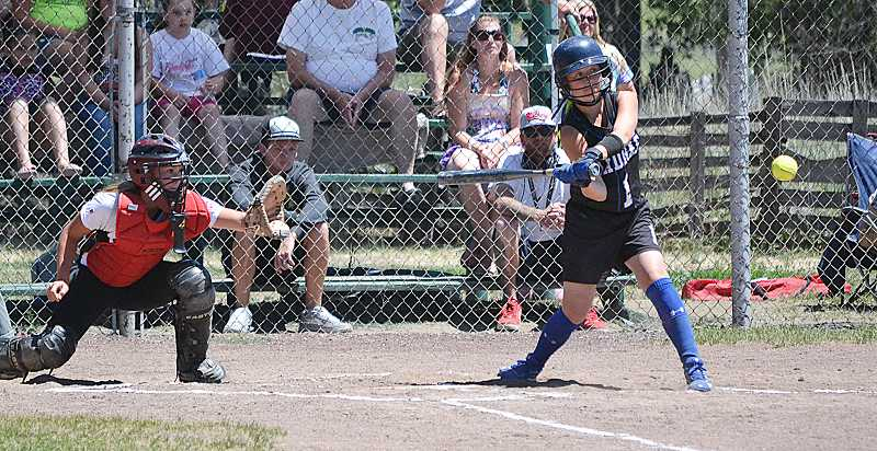 by: PHOTO BY ANNA WILLARD FOR THE PIONEER - Jefferson County leftfielder Kelsie Mitchell hits a single in the top of the second inning to score one run in the first round of the Oregon State Junior Softball Championships on Saturday in Klamath Falls.