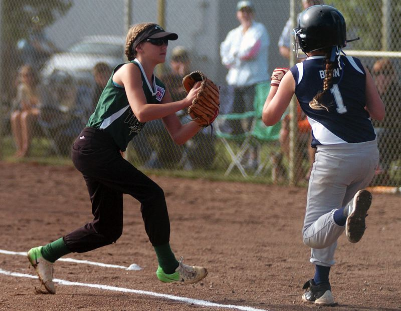 by: DAN BROOD - DEFENSIVE -- Tigard first baseman Abby Soderquist (left) gets ready to tag out Hood River's Solilo Brun during Friday's opening game at the Oregon Little League state tournament.