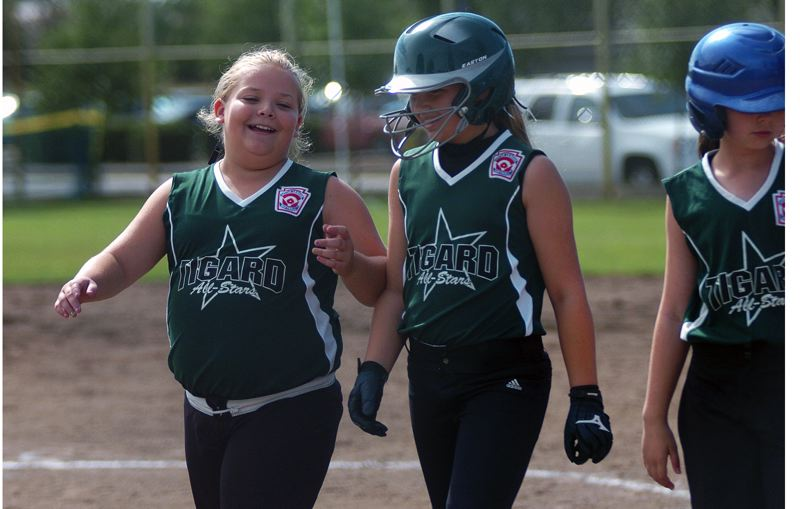by: DAN BROOD - WINNING SMILES -- Tigard's Victoria Vanderburg (left) and Taylor Corcoran are all smiles following the team's victory over Hood River.