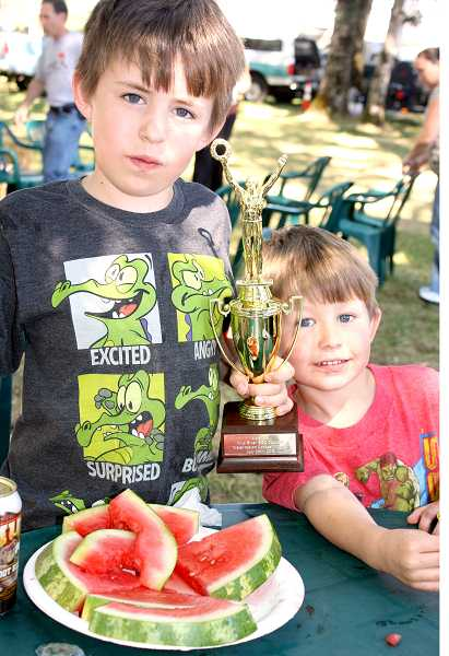 by: PEGGY SAVAGE - Jack Scymanky, 7, shows off his trophy for winning the watermelon eating contest with his brother, Tyler, 4 at the Wild River BBQ in Molalla, Saturday