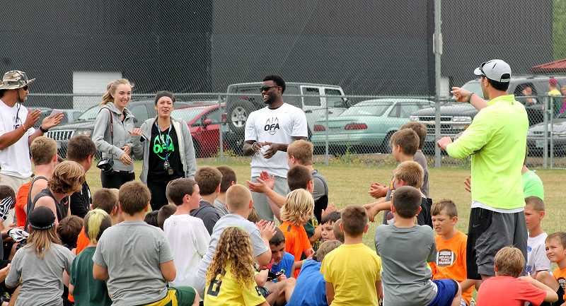 by: CORY MIMMS - Young athletes gather around Seahawks cornerback Walter Thurmond, during a youth football camp on Saturday, July 20, in Molalla, Ore.