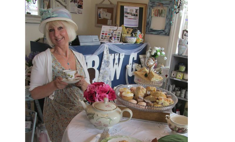 by: PHOTO BY ELLEN SPITALERI - Cheryl Frampton, owner of Big White Goose in Oregon City, relaxes with a cup of tea, as she gets ready for her English tea party on Aug. 10.