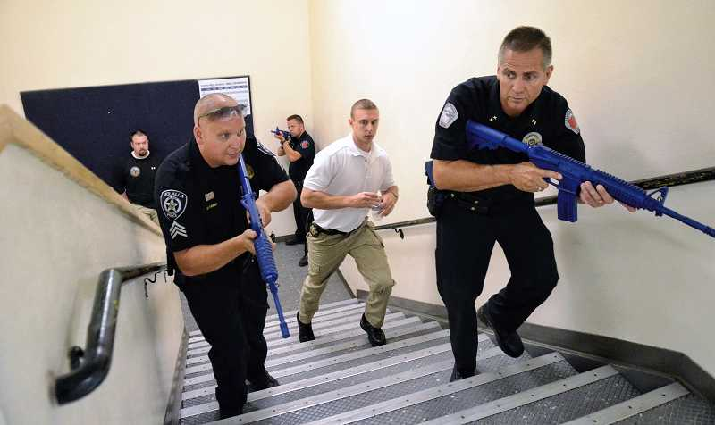 by: RAY HUGHEY - Canby Police Chief Bret Smith, at right, and Molalla Police Sgt. Chris Long advance up a staircase during the active shooter response training this month.