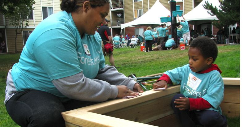 by: OUTLOOK PHOTO: LISA K. ANDERSON - Mackarius, 4, helps his mom, Rebecca Jones, a Southeast Portland resident and Foresters volunteer, sand a garden box at Saturday's build.