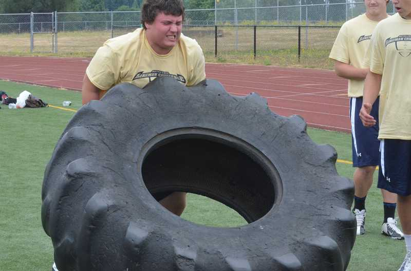 by: JEFF GOODMAN - Austin Schwartz tries to flip a 350-pound tractor tire July 20 during the fourth-annual Metro Area Lineman Challenge at Tualatin High School. He and seven other Canby football players participated in the event.